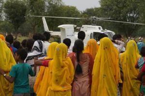 Folk stimler sammen om helikopteren før flyvning i Indien